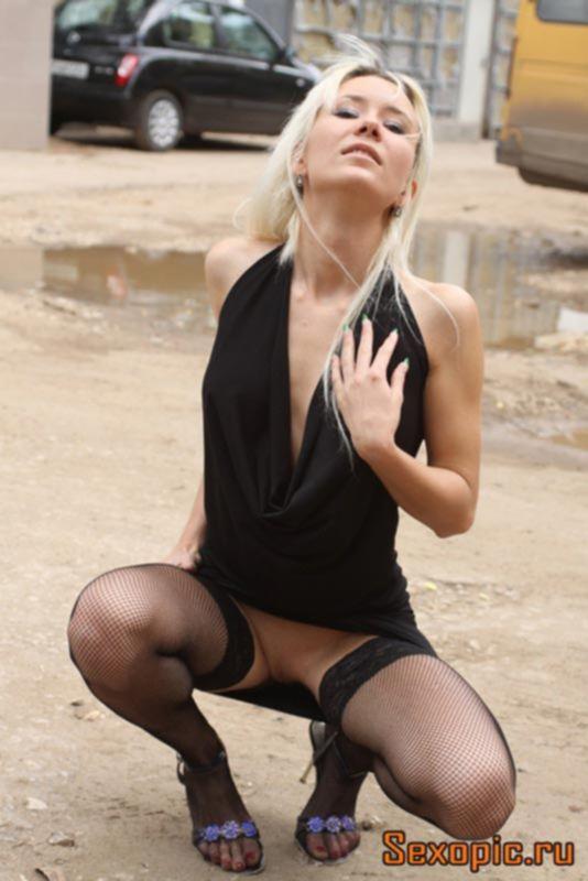 Девушка в коротком платье без трусов позирует на улице, эротика