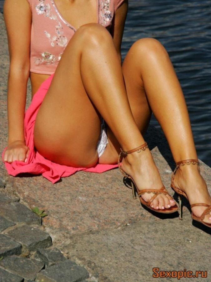 Девушка в розовой юбке показывает апскирт на улице